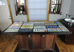 Home bar built out of circa 1930 recycled doors and old license plates for bar top