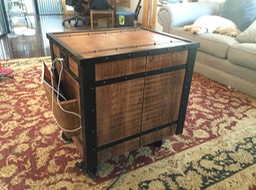 Industrial end table made from wormy chestnut wood (reclaimed from house built in early 1900's).   Custom made steel structure with welded old style rivets, then powder coated.  Three drawers with old tools attached for handles. Integrated outlet with usb charging port.